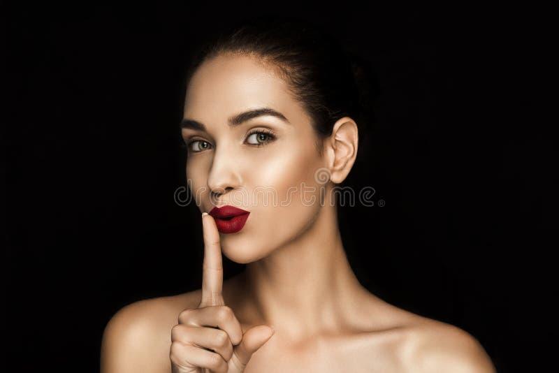 Mulher sedutor bonita com shh símbolo fotografia de stock royalty free