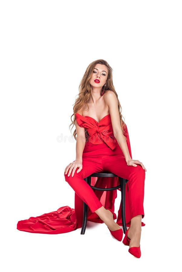 mulher sedutor bonita que levanta na roupa vermelha na cadeira fotos de stock royalty free