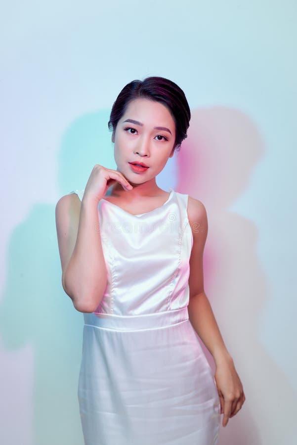 Mulher sedutor luxuosa de surpresa no vestido de partido branco à moda que levanta na parede branca Retrato da forma Comemorando  fotografia de stock