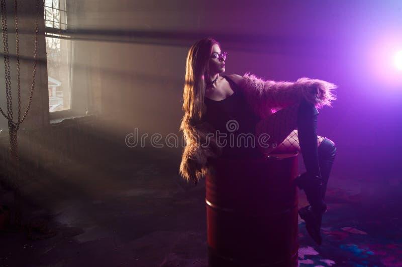 Mulher sedutor nova, retrato na escuridão Menina no casaco de pele e em vidros cor-de-rosa à moda imagens de stock