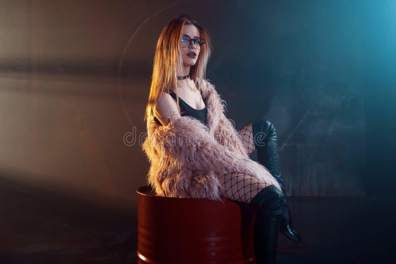Mulher sedutor nova, retrato na escuridão Menina no casaco de pele e em vidros cor-de-rosa à moda foto de stock royalty free