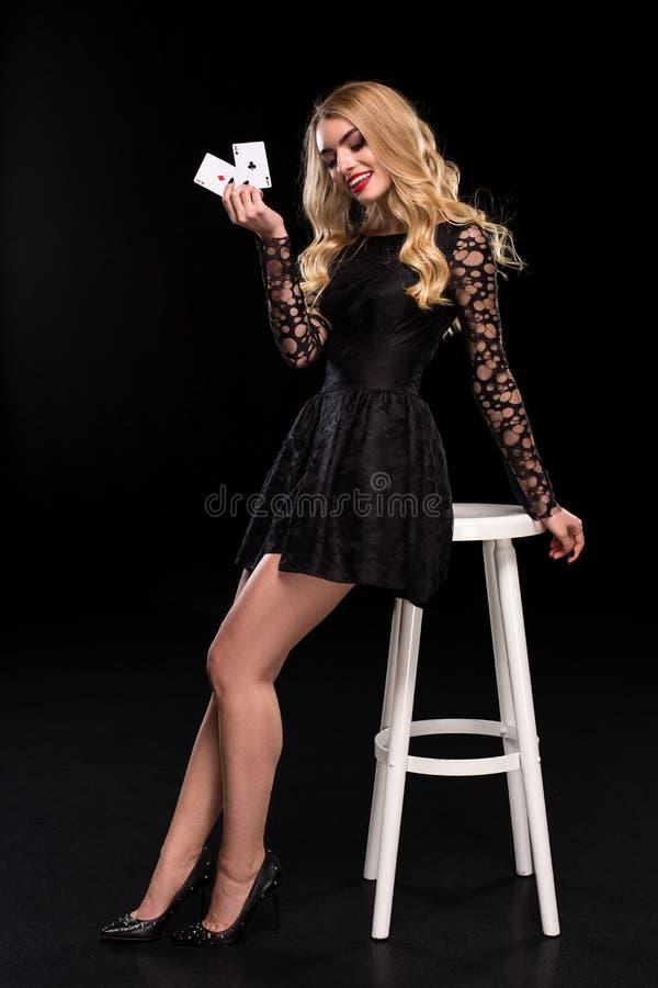 Mulher segura bonita que senta-se na cadeira que mostra os cartões que olham a câmera com lugar da cópia foto de stock