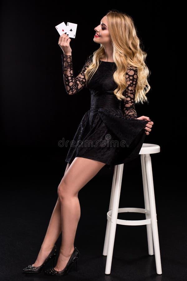Mulher segura bonita que senta-se na cadeira que mostra os cartões que olham a câmera com lugar da cópia fotografia de stock royalty free