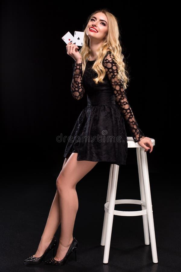 Mulher segura bonita que senta-se na cadeira que mostra os cartões que olham a câmera com lugar da cópia imagens de stock