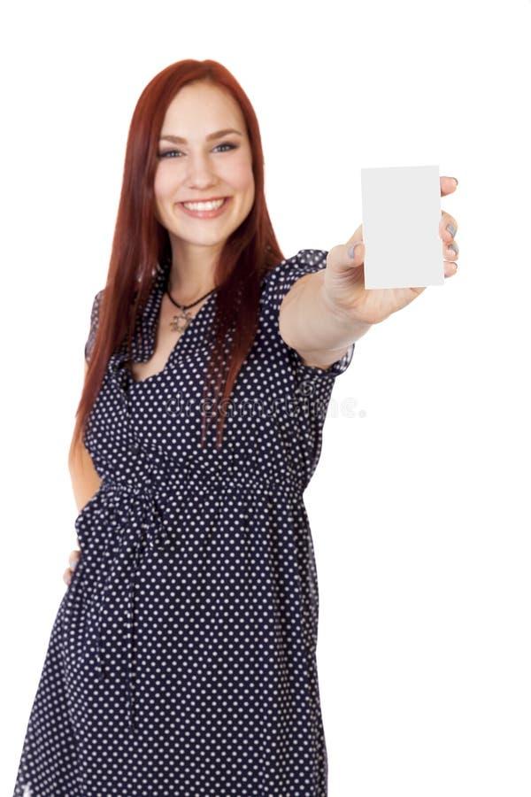 A mulher segura com cabelo vermelho mantém um cartão vazio vertic foto de stock royalty free