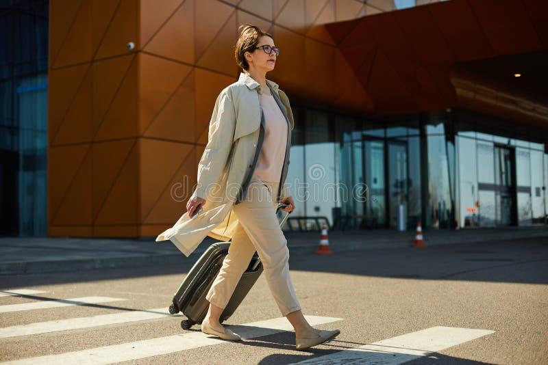Mulher segura com a rua do cruzamento da bagagem imagem de stock royalty free