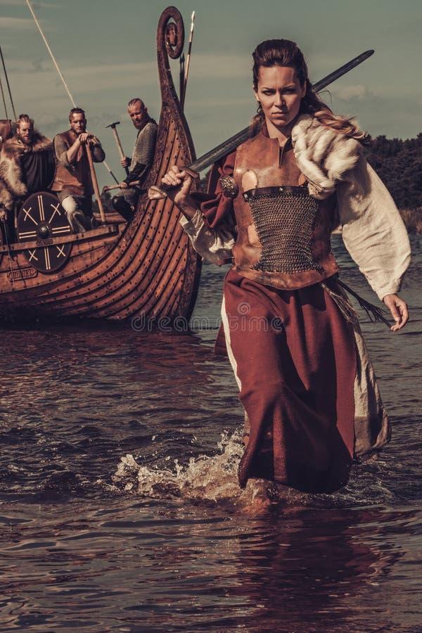 Mulher segura de viquingue com espada que anda ao longo da costa com o Drakkar no fundo fotos de stock royalty free