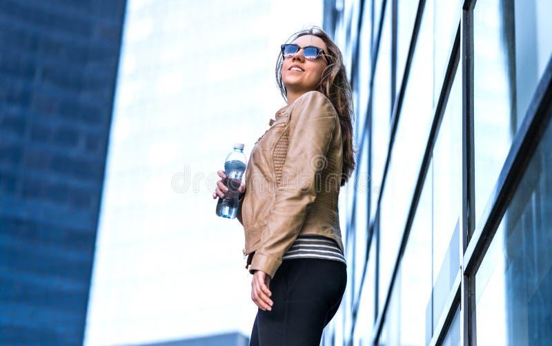 Mulher segura na cidade com garrafa de água foto de stock royalty free