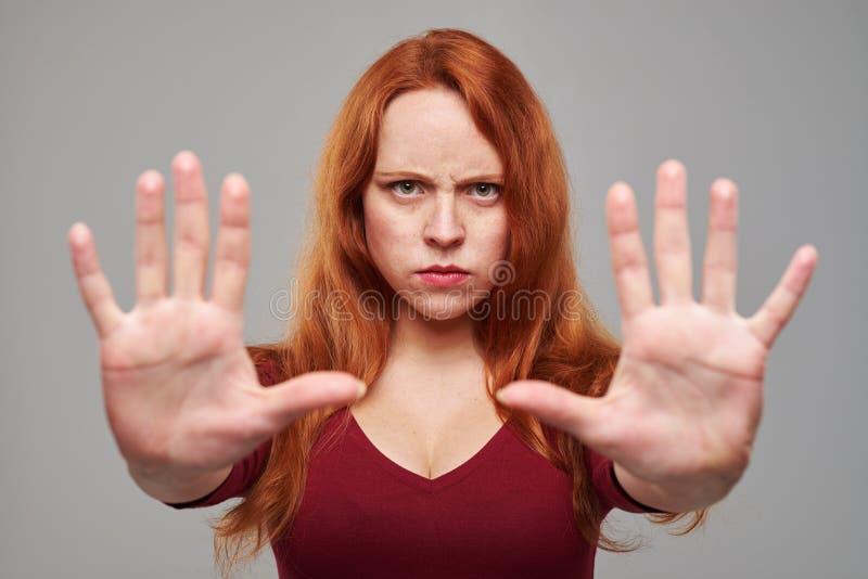 A mulher segura que gesticula a parada canta com duas mãos imagens de stock royalty free