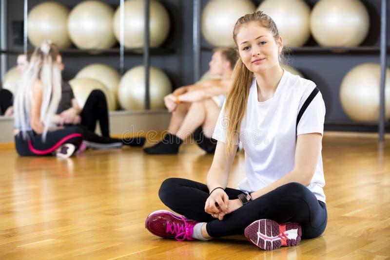 Mulher segura que senta equipado com pernas transversal no fitness center fotos de stock royalty free