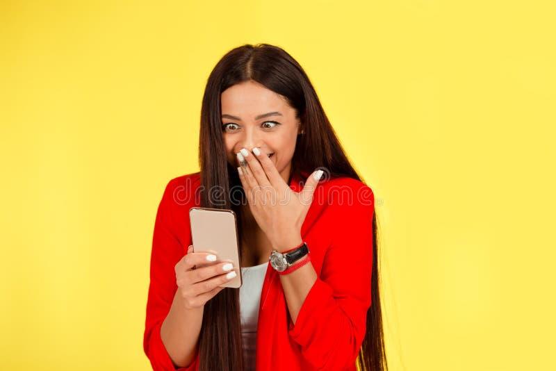 Mulher segurando celular examinando-o com cara surpreendente, olhos grandes isolaram o pano de fundo amarelo fotos de stock royalty free
