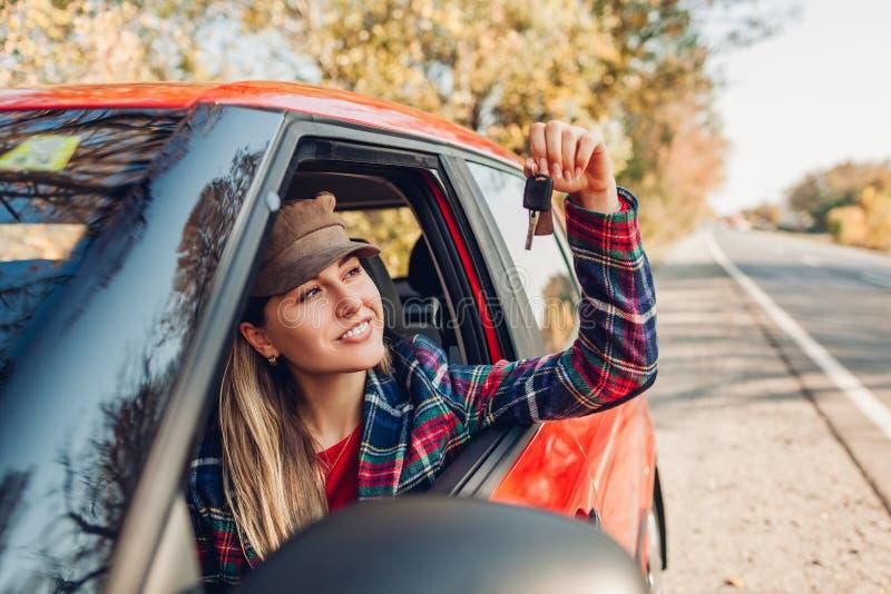 Mulher segurando chaves do carro novo Comprador feliz adquiriu o automóvel vermelho Driver olhando as teclas sentadas em automáti fotografia de stock