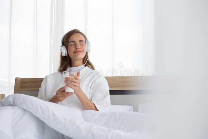 Mulher segurando um copo de leite e ouvindo música relaxante na aplicação musical de manhã na cama foto de stock