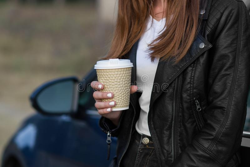 Mulher segurando xícara com café quente perto de um carro foto de stock royalty free