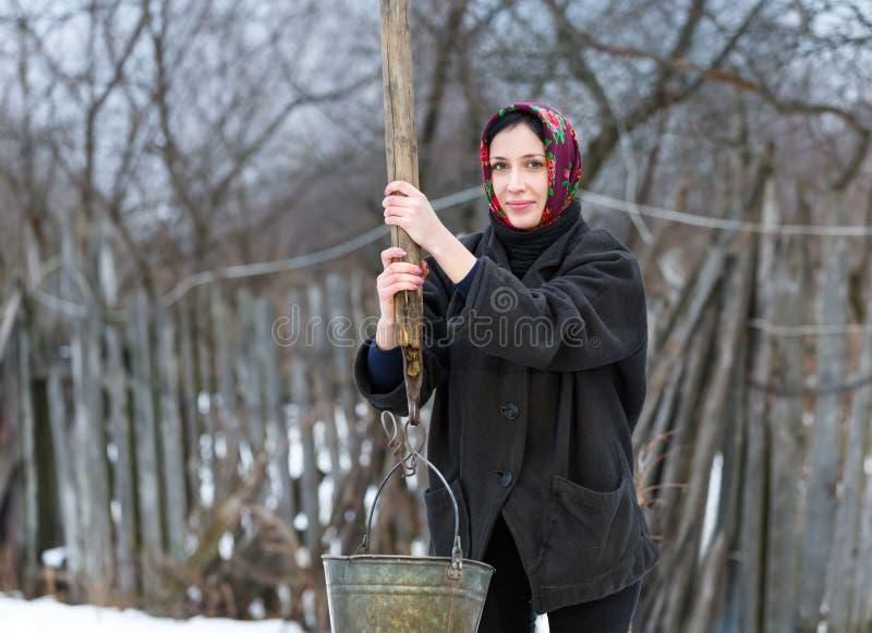 A mulher seleciona a água do poço fotografia de stock royalty free