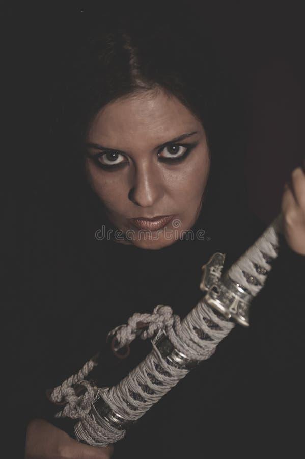 Mulher selvagem do guerreiro com a espada do cabelo preto e do ferro fotos de stock royalty free