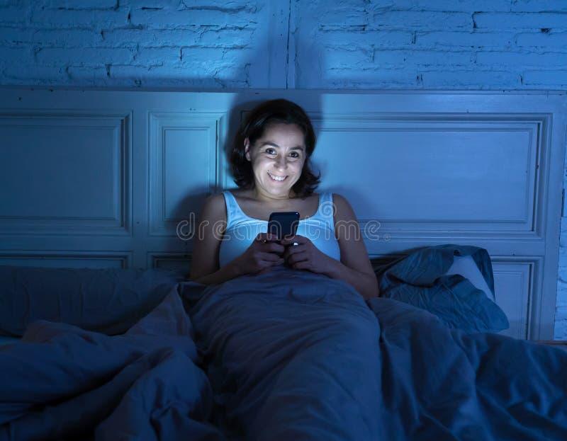 Mulher sem sono feliz que encontra-se na cama no Internet usando o telefone celular tarde na noite no quarto escuro fotografia de stock