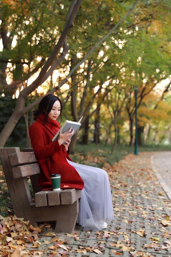 Mulher sensual asiática nova que lê um livro no cenário romântico do outono Retrato da moça bonita na floresta outonal fotografia de stock royalty free