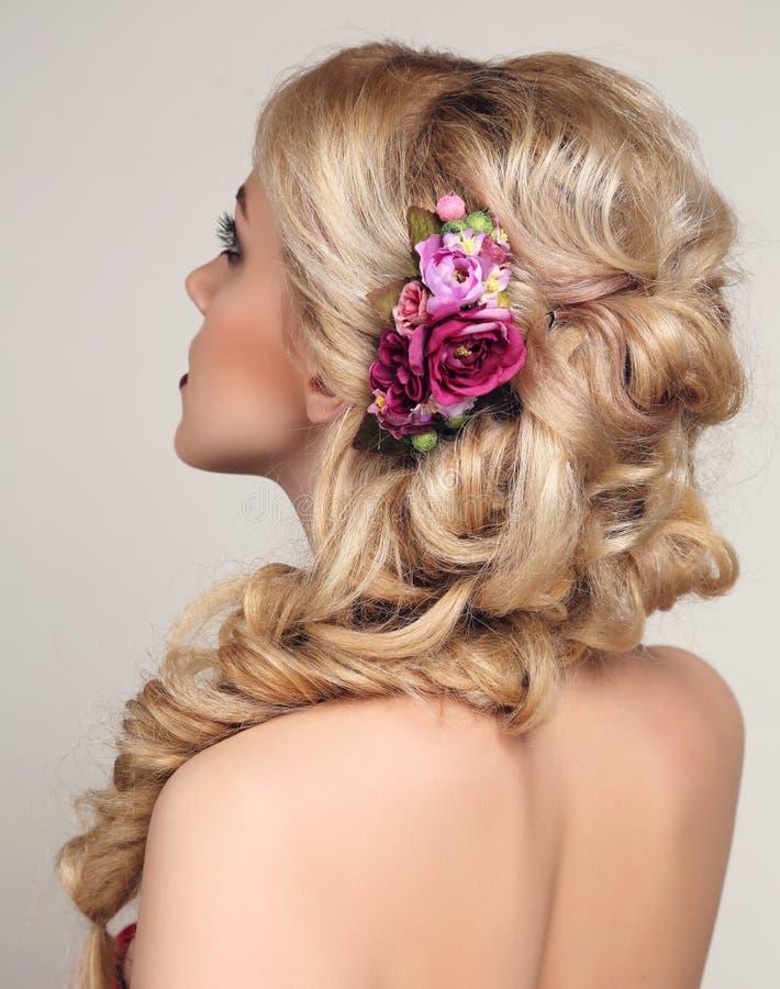 Mulher sensual bonita com o acessório louro do cabelo encaracolado e da flor imagem de stock