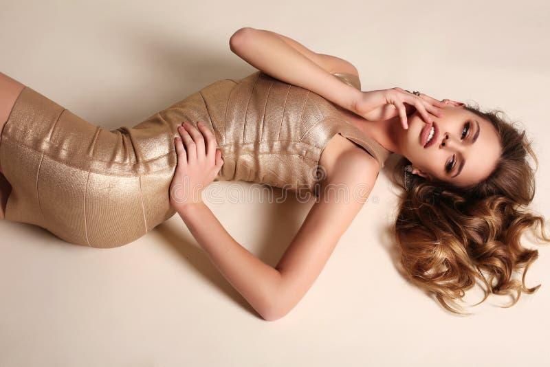 Mulher sensual com cabelo encaracolado louro no vestido elegante do ouro imagem de stock