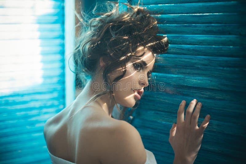 Mulher sensual com composição na janela menina elegante com cabelo elegante Mulher da forma com composição e cabelo encaracolado imagem de stock