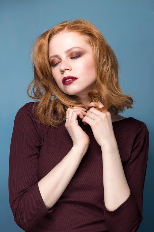 Mulher sensual do ruivo com os olhos fechados no fundo azul imagens de stock royalty free