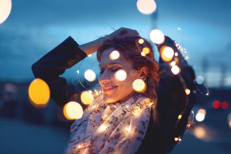 Mulher sensual do ruivo que joga com luzes feericamente da festão na noite foto de stock
