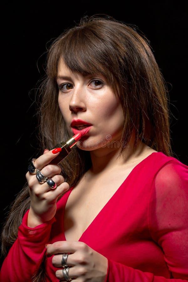 Mulher sensual elegante que aplica o batom vermelho fotos de stock