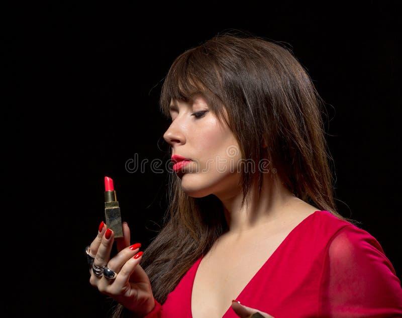 Mulher sensual elegante que aplica o batom vermelho imagem de stock royalty free