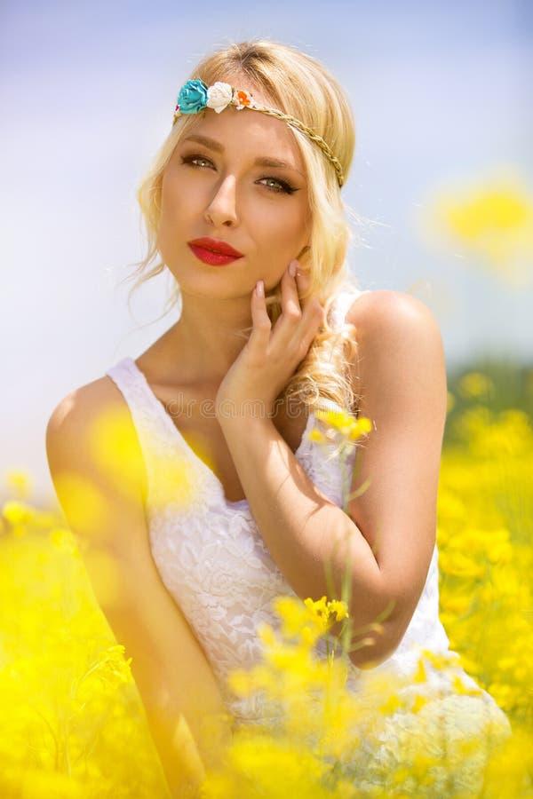 Mulher sensual em flores amarelas foto de stock royalty free