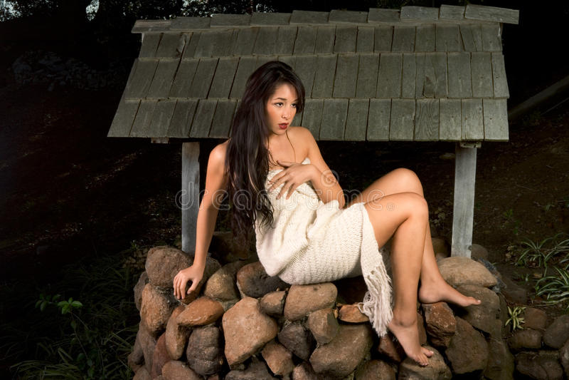 Mulher sensual envolvida no lenço ao ar livre pelo poço fotografia de stock royalty free