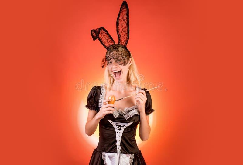 A mulher sensual está preparando-se para o feriado de easter A pintura feliz da jovem mulher eggs em um fundo alimentado Easter f fotografia de stock