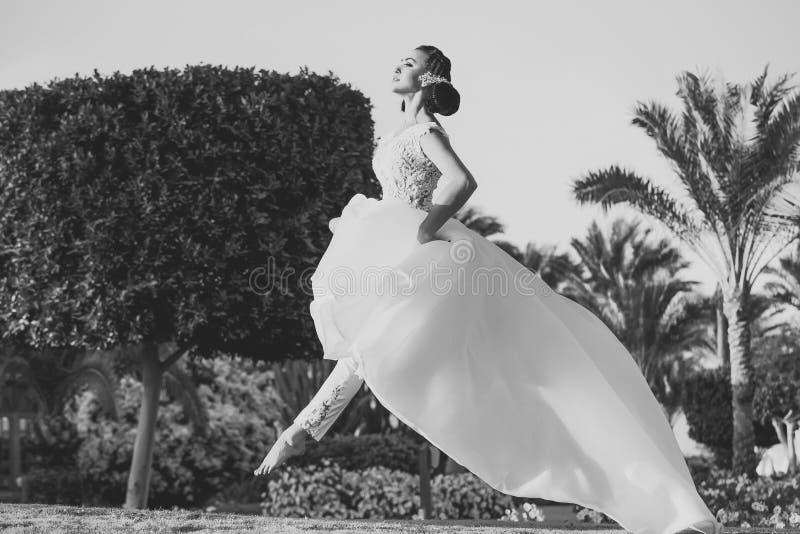Mulher sensual A menina que salta na grama verde na paisagem tropical imagem de stock royalty free