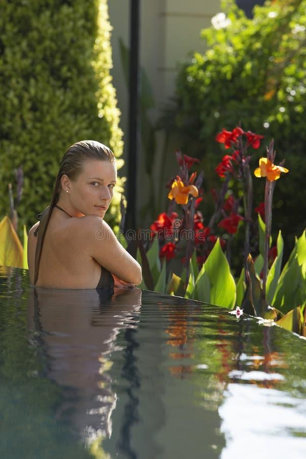 Mulher sensual na piscina exterior fotografia de stock royalty free