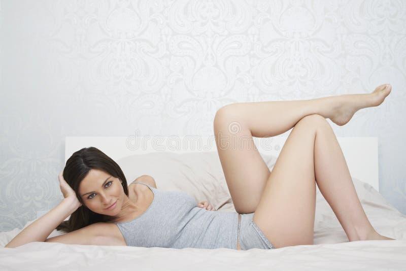 Mulher sensual no Nightwear que encontra-se na cama imagem de stock royalty free