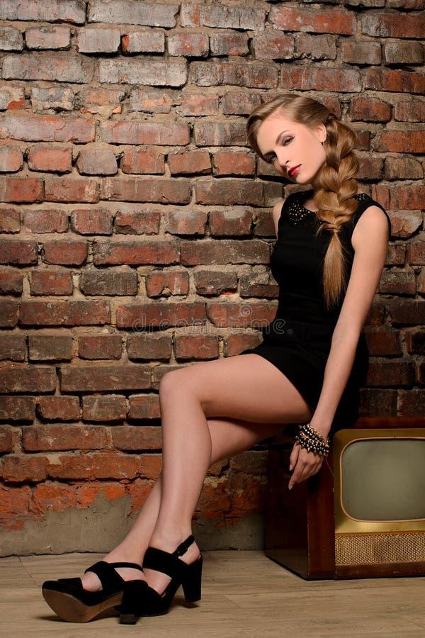 Mulher sensual nova que senta-se no aparelho de televisão retro fotos de stock