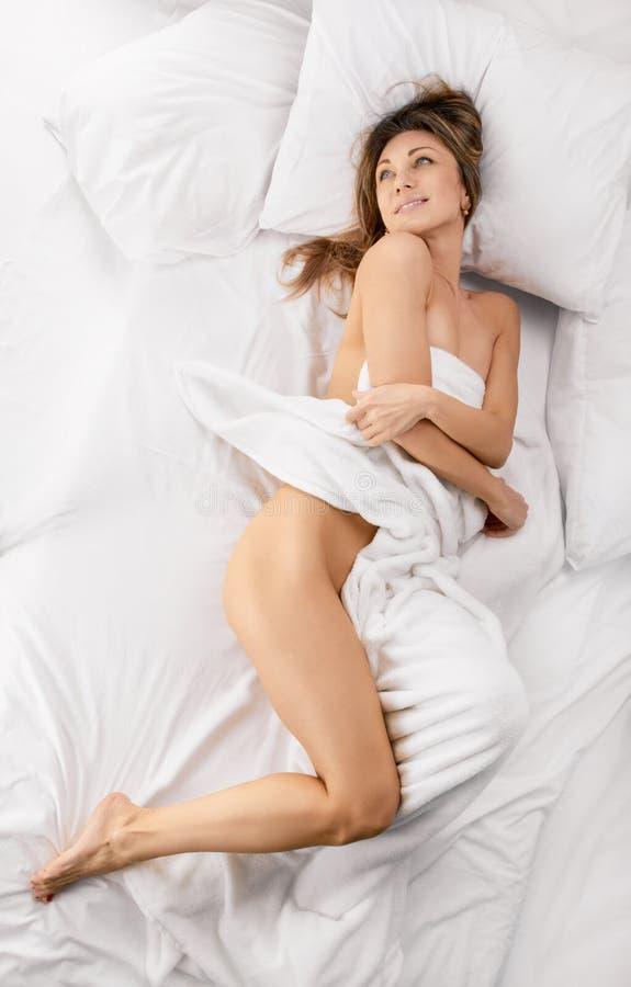 Mulher sensual que coloca na cama fotografia de stock