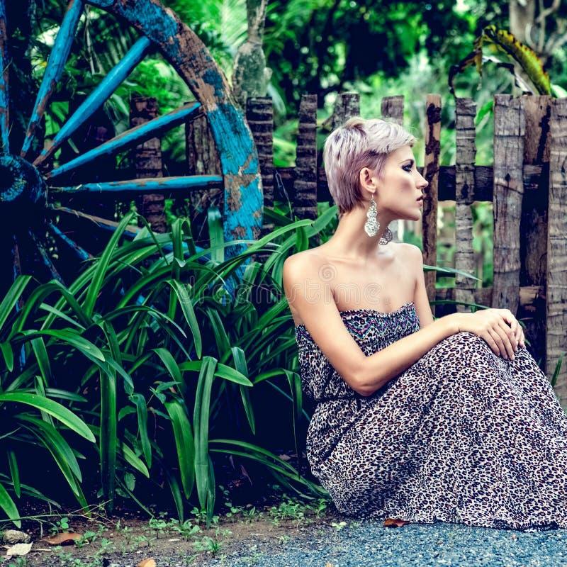 mulher sensual que senta-se na floresta fotografia de stock royalty free