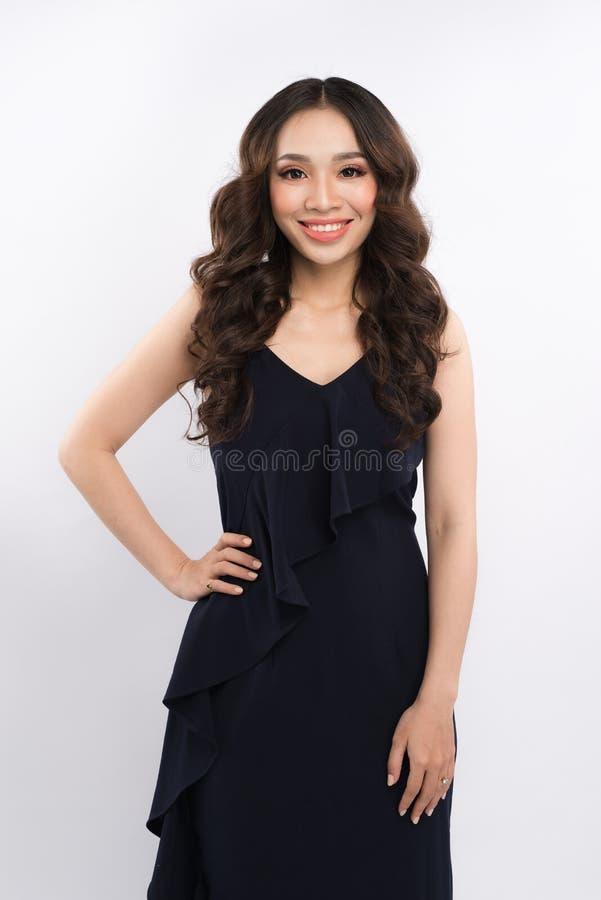 Mulher sensual que veste um vestido preto sobre o fundo cinzento imagens de stock royalty free
