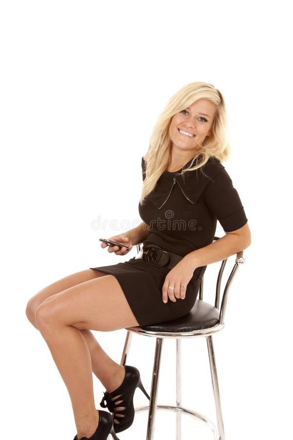 A mulher senta o telefone do sorriso do vestido foto de stock royalty free