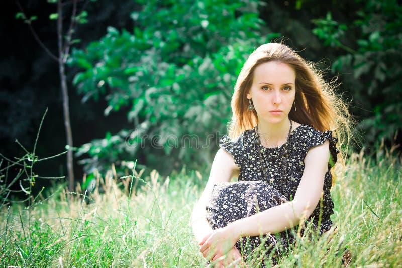 A mulher senta-se em um prado e olha-se a câmera imagens de stock royalty free