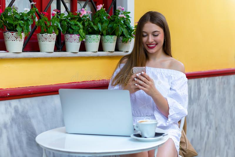 A mulher senta-se em uma cervejaria e trabalha-se no portátil e no smartphone fotografia de stock