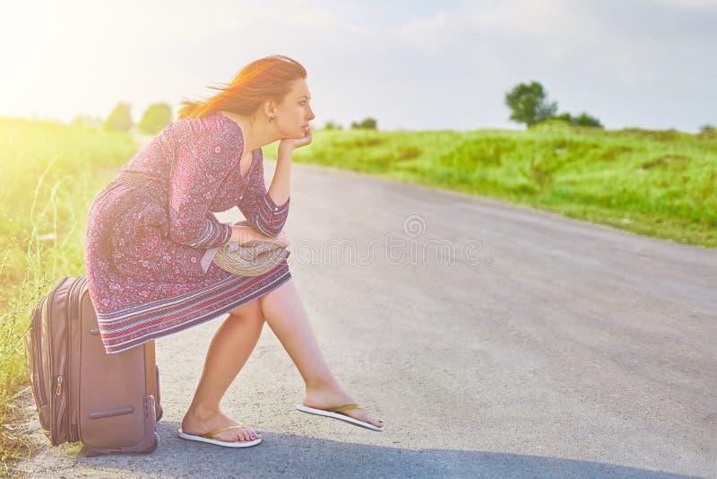 A mulher senta-se na bagagem fotos de stock royalty free