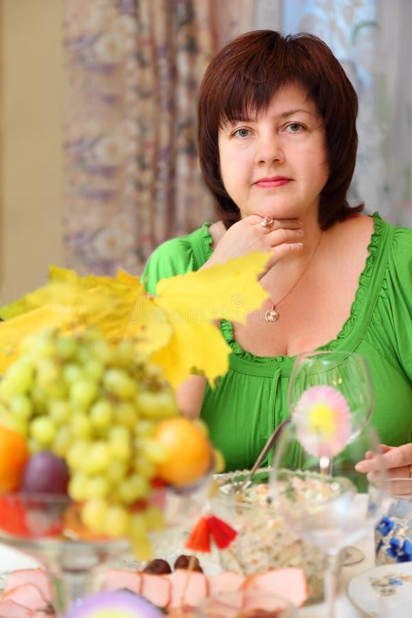 A mulher senta-se na tabela de banquete foto de stock royalty free