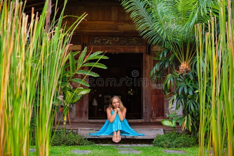 A mulher senta-se na varanda de madeira do bungalow com opinião tropical do jardim foto de stock royalty free