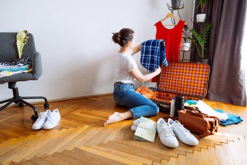 A mulher senta-se no assoalho roupa da embalagem para a viagem conceito do curso Copie o espaço foto de stock
