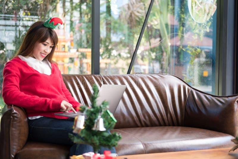 A mulher senta-se no sofá em casa computador do uso da menina durante o xmas christ foto de stock