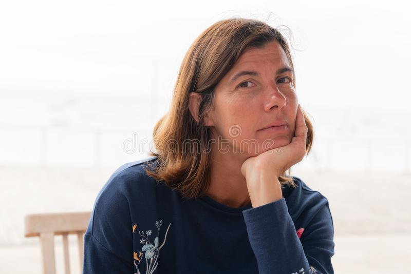 Mulher sentada em terrace cafe praia com vista oceânica mão no queixo imagens de stock royalty free