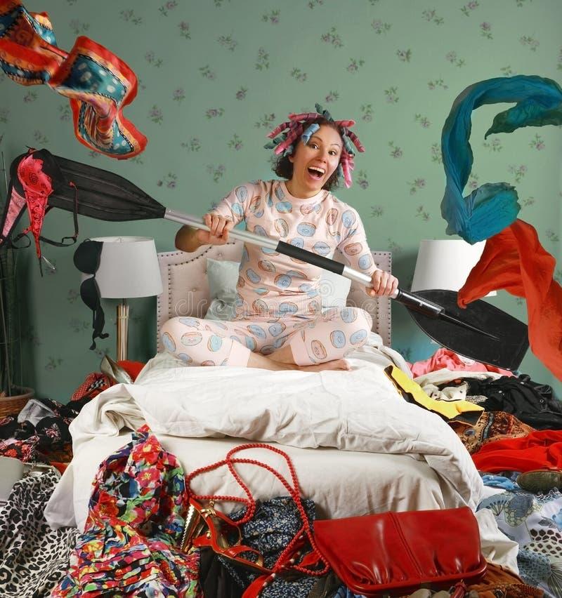 Mulher sentada numa cama remo como se estivesse num barco imagem de stock