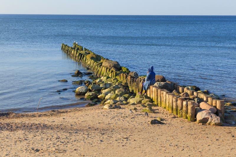 Mulher sentada sozinha em um velho quebra-mar imagem de stock